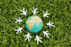 Paper people in a circle with green grass background Stock Images