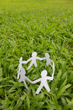 Paper people in a circle with green grass background Royalty Free Stock Images