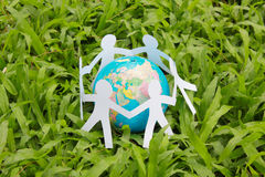 Paper people in a circle with green grass background. World peace concept stock images