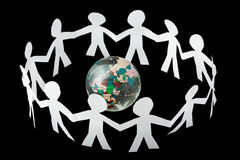 Paper people cutouts sing and dance around globe. Paper little people cutouts sing and dance in ring around small globe isolated on black background Stock Image