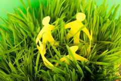 Paper people on green grass Stock Image