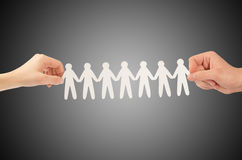 Paper people in hands. Isolated on a black background Royalty Free Stock Photos