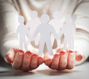 Paper people in hands in gesture of giving, presenting. Concept Royalty Free Stock Photos