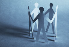 Paper people holding for hands. On blue background Royalty Free Stock Image