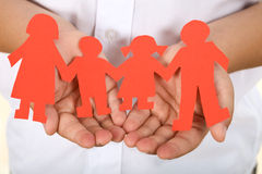 Paper people holding hands - family concept. Paper people holding hands in child palm - happy family concept stock image