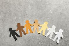 Paper people holding hands on grey background. Top view. Unity concept stock photo