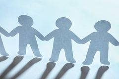 Paper people holding hands on light background. Unity concept royalty free stock photo