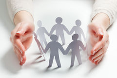 Paper people surrounded by hands in gesture of protection. Concept of insurance Stock Photo