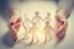 Paper people surrounded by hands in gesture of protection. Concept of insurance Royalty Free Stock Photography