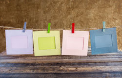 Paper photo frame on clothesline on grunge background Royalty Free Stock Photos