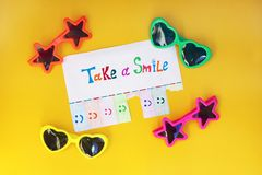 A paper with the phrase: Take a Smile and with a smile sign ready to be tore off Stock Photos
