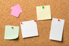 Pinned paper notes on cork board Stock Image