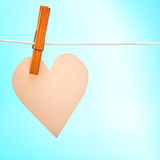 Paper pink heart. Hanging on twine against blue paper texture for Valentines day stock image