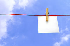 Paper pinned. In a line with the sky in the background Stock Photo