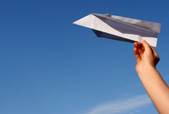 Paper plane. Holding a paper airplane against a blue sky Royalty Free Stock Images