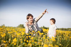 Paper plane. Happy dad and son launch paper plane in the field of dandelions Royalty Free Stock Images