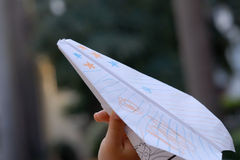 Paper plane. A boy is taking a paper plane, painting some stars on it Stock Photos
