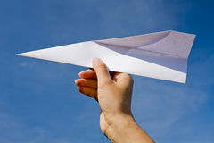 Paper plane. Hand throwing a paper plane royalty free stock photo