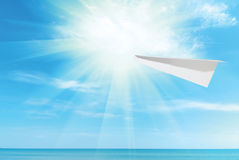 Paper plane against the blue sky and sea Stock Photo