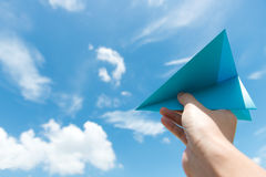 Paper plane against cloudy sky. Hand launching paper plane toward cloudy blue sky Stock Image