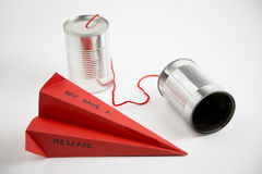 Paper plane and cans for a simple communication. Metaphor on the ease with which it can communicate by shortening the distance between people Stock Photography
