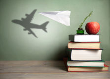 Paper plane concept. Paper plane with shadow of an aircraft next to a stack of books, quill and apple royalty free stock images
