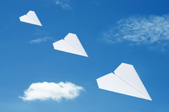 Paper plane flying over clouds with blue sky. Royalty Free Stock Photos