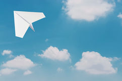 Paper plane flying over clouds with blue sky. Royalty Free Stock Images