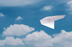 Paper plane flying over clouds with blue sky. Stock Photography