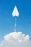 Paper plane flying up, over clouds with blue sky. Royalty Free Stock Image
