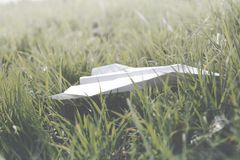 Paper plane landed on a green lawn stock images