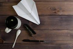 Paper plane, mug, spoon, stapler, black handle Stock Photos