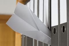 Paper Plane stuck between folders Stock Photos