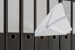 Paper Plane stuck between folders Stock Photo