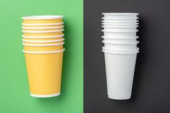 Paper and plastic mugs on green and black background stock photo