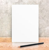 Paper poster frame and black pencil at concrete wall and wooden Stock Photography