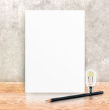 Paper poster frame and black pencil at concrete wall and wooden Royalty Free Stock Photo