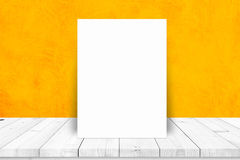 Paper poster lean on white table with yellow wall. Royalty Free Stock Image