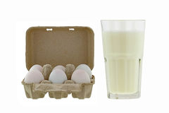 Paper pulp egg tray packages of fresh eggs next to glass of fres Stock Photography