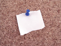Paper with push pin. White scrap of paper with blue push pin on cork board royalty free stock images