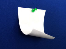 Paper and push pin. A small paper note on a blue board Stock Photos