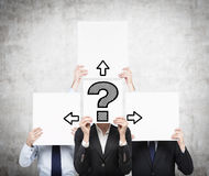 Paper with question mark and arrow. Businesspeople holding paper with drawing question mark and arrow Stock Images