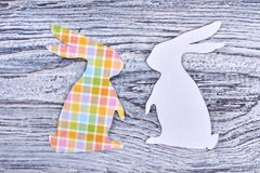 Paper rabbit cutouts, top view. Couple of white and patterned Easter bunnies on rustic wooden background. Papercut animalistic silhouettes for Easter holidays royalty free stock photography