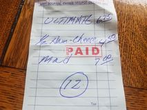 Paper receipt with word paid and ham and cheese sandwich and dollar amounts royalty free stock photos