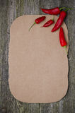 Paper for recipe and chili peppers on old wooden background Royalty Free Stock Images