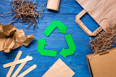 Paper recycle sign with paper and carton garbage on blue wooden background top view Stock Photos