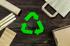 Paper recycle sign with paper and carton garbage on wooden background top view Royalty Free Stock Photography
