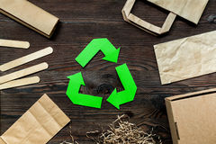 Paper recycle sign with paper and carton garbage on wooden background top view Stock Images