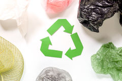 Paper recycle sign with plastic garbage on white background top view Stock Photo
