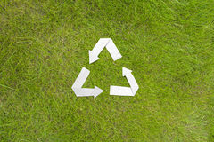 Paper recycle symbol on green grass Royalty Free Stock Image
